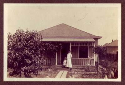Jesús (García) Alvarado (1871-1966) with daughter outside the family home at 717 Bailey Street in Los Angeles